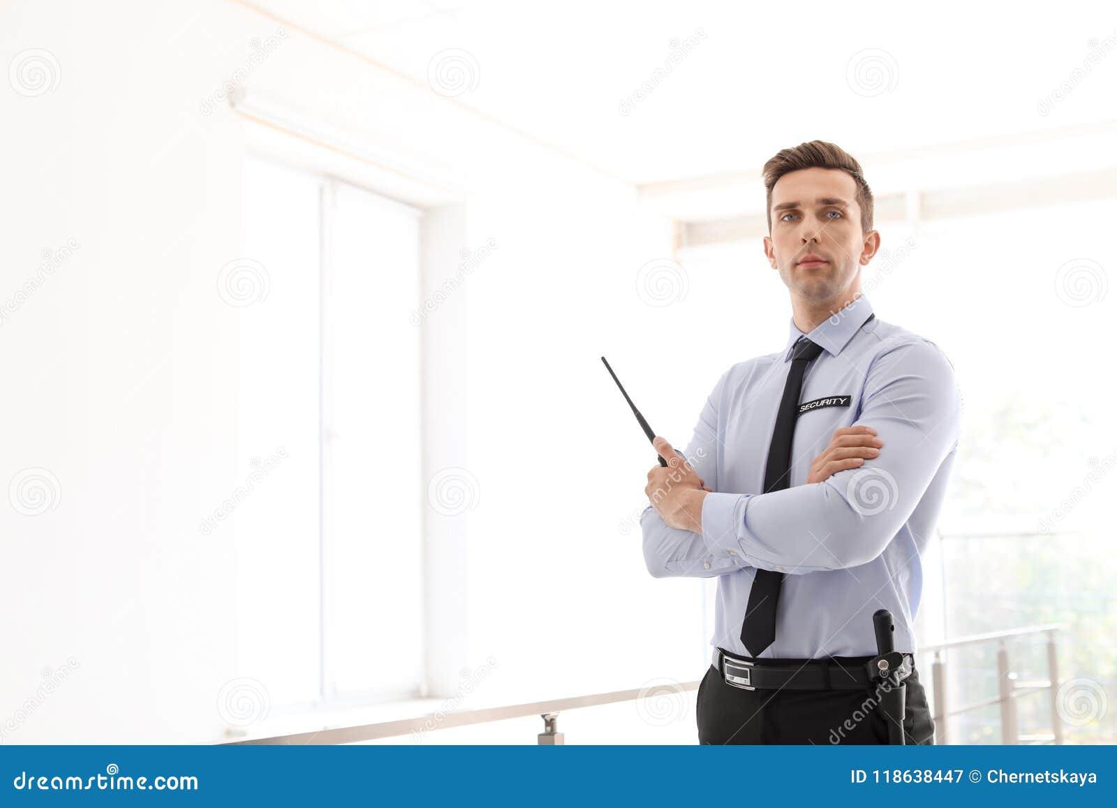 Guardia de seguridad masculino con el transmisor de la radio portátil