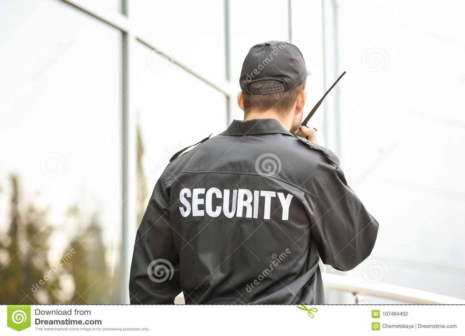 Guardia de seguridad masculino usando transmisor de la radio portátil