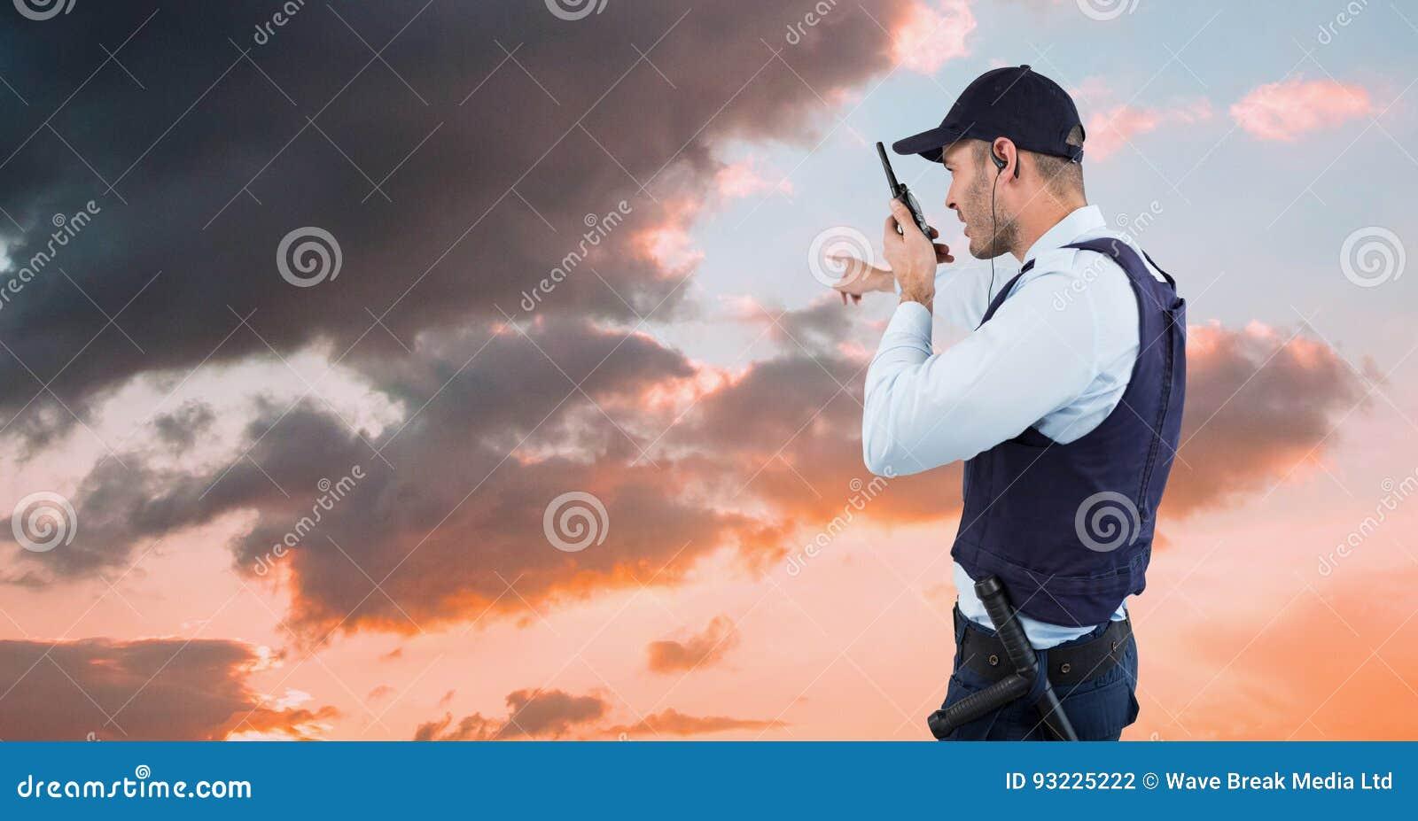 Guardia giurata che gesturing e che parla sul walkie-talkie mentre affrontando verso il cielo