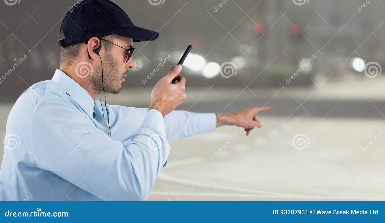 Guardia giurata con il walkie-talkie che indica contro la via confusa
