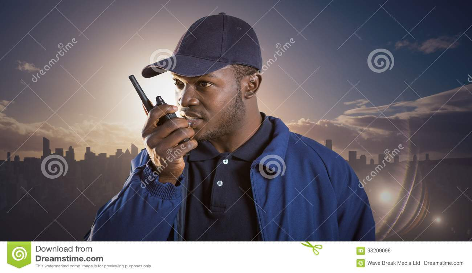 Guardia giurata con il walkie-talkie contro orizzonte ed il tramonto