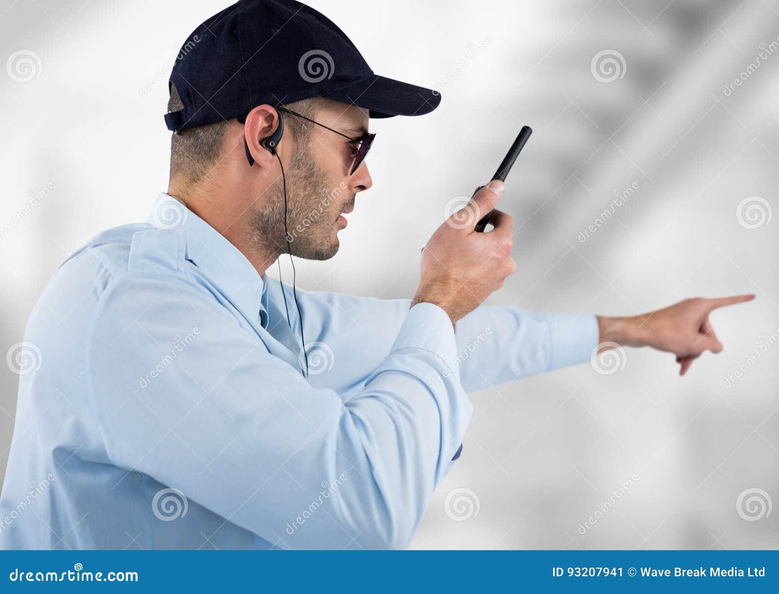 Guardia giurata con le cuffie e parlare con il walkie-talkie Fondo vago luce