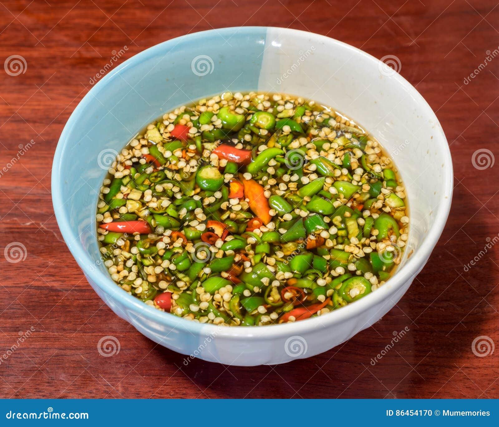 Guarnisca i peperoncini rossi affettati sulla salsa del sale in tazza