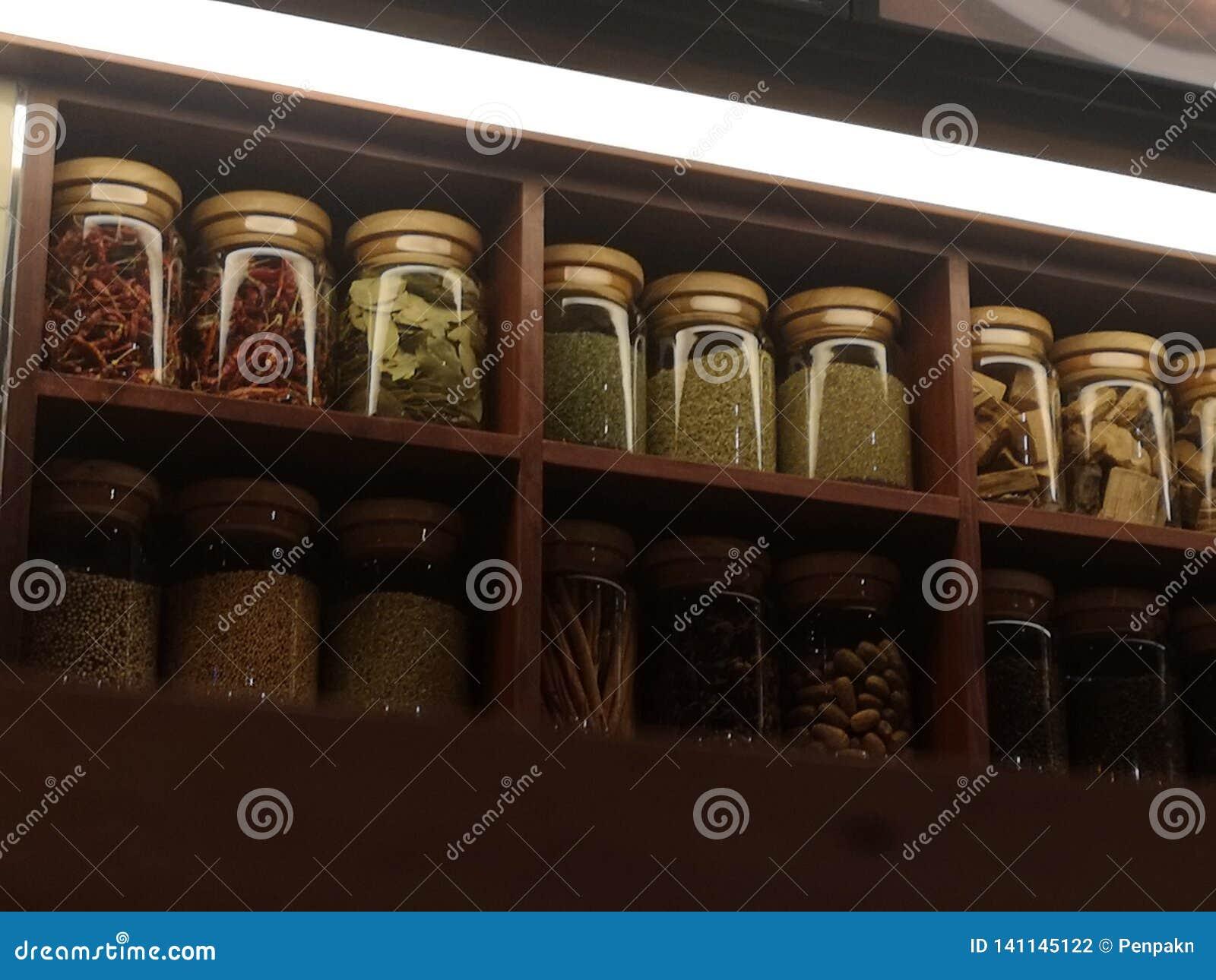Guarnisca la roba asciutta imballata nello scaffale di legno delle bottiglie di vetro trasparente