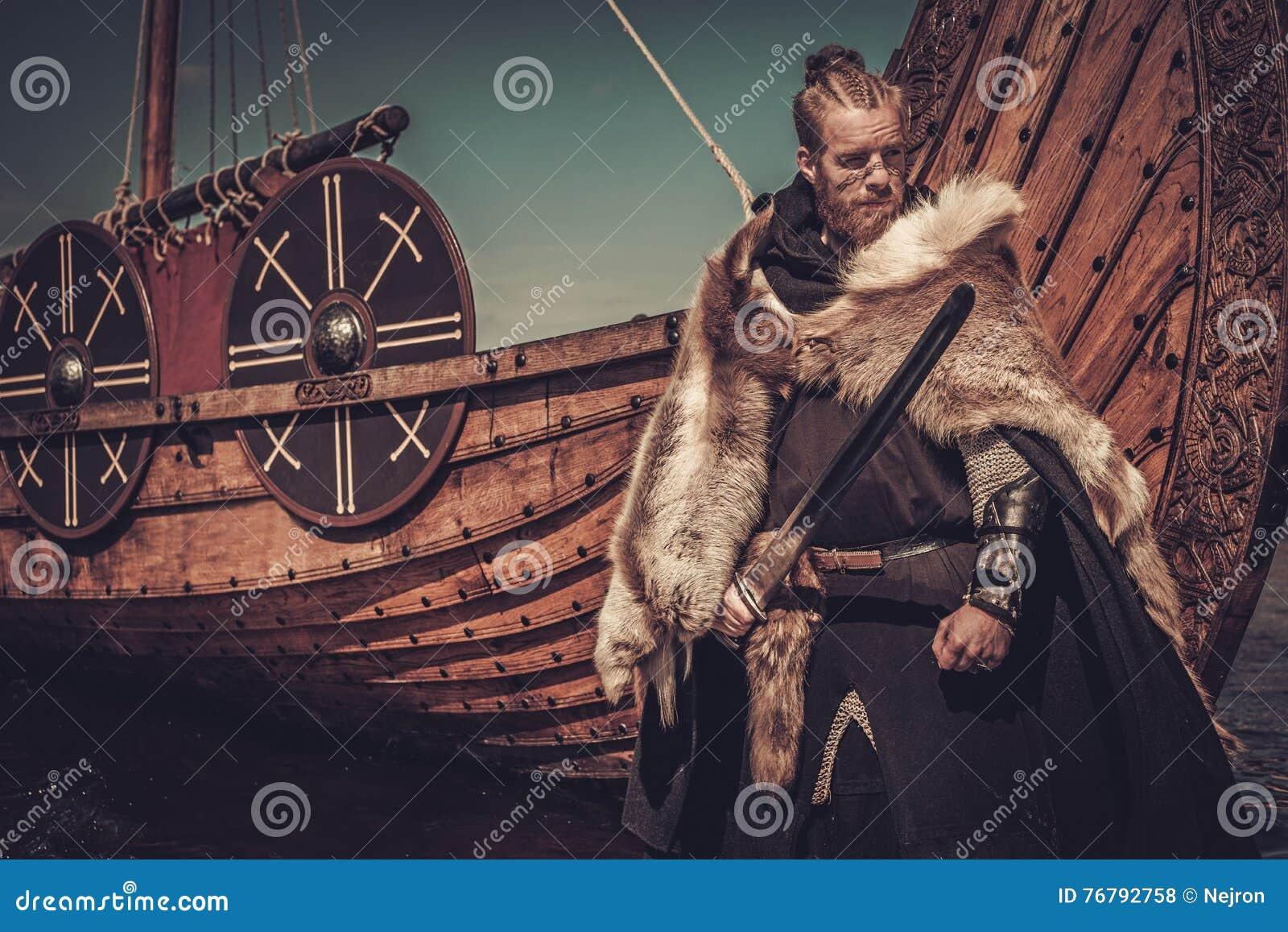 Guerrero de Viking con la espada que se coloca cerca de Drakkar en la costa