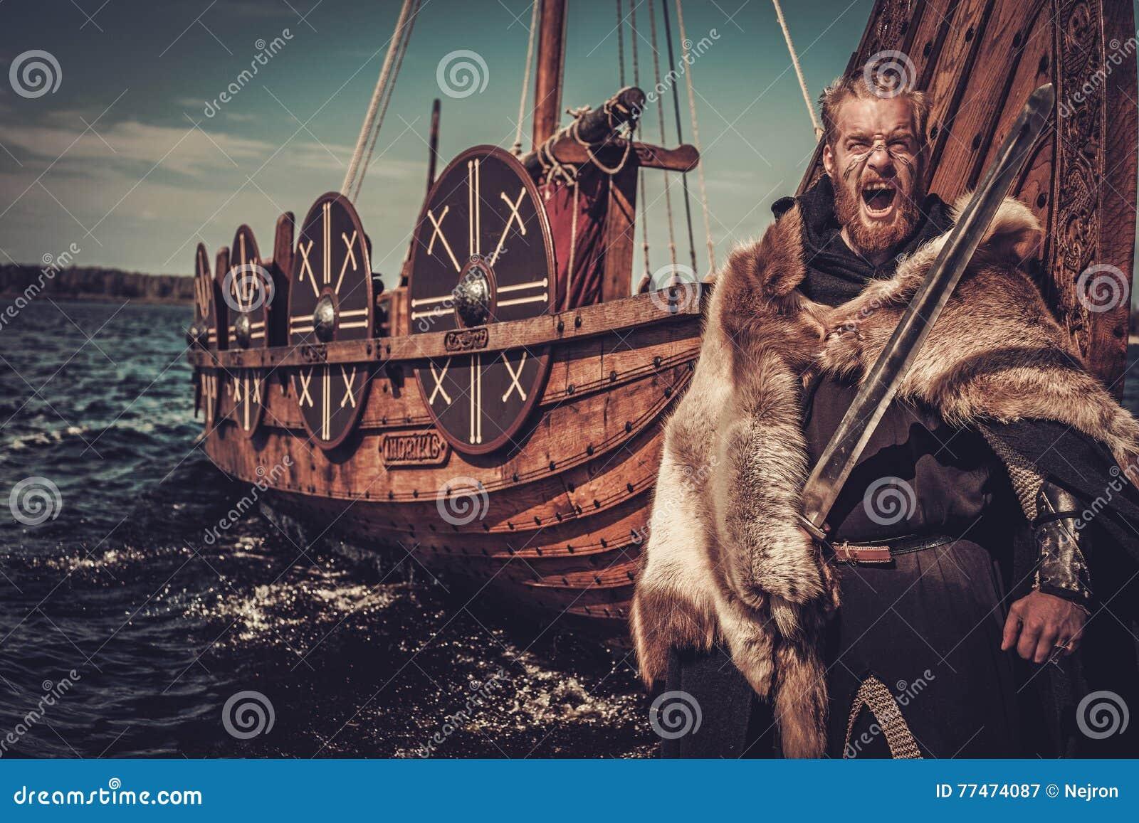 Guerrero de Viking con la espada y el escudo que se colocan cerca de Drakkar en la costa