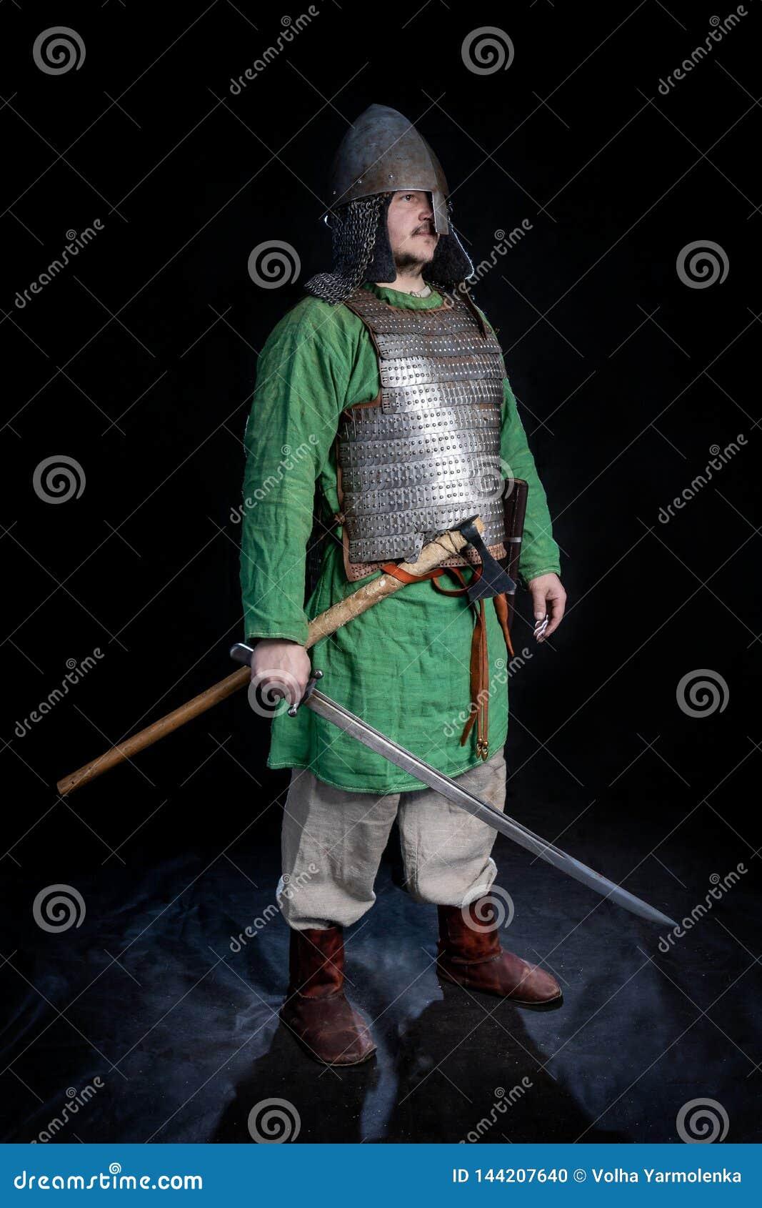 Guerriero di età di vichingo dello slavo in armatura e casco con la spada e l ascia