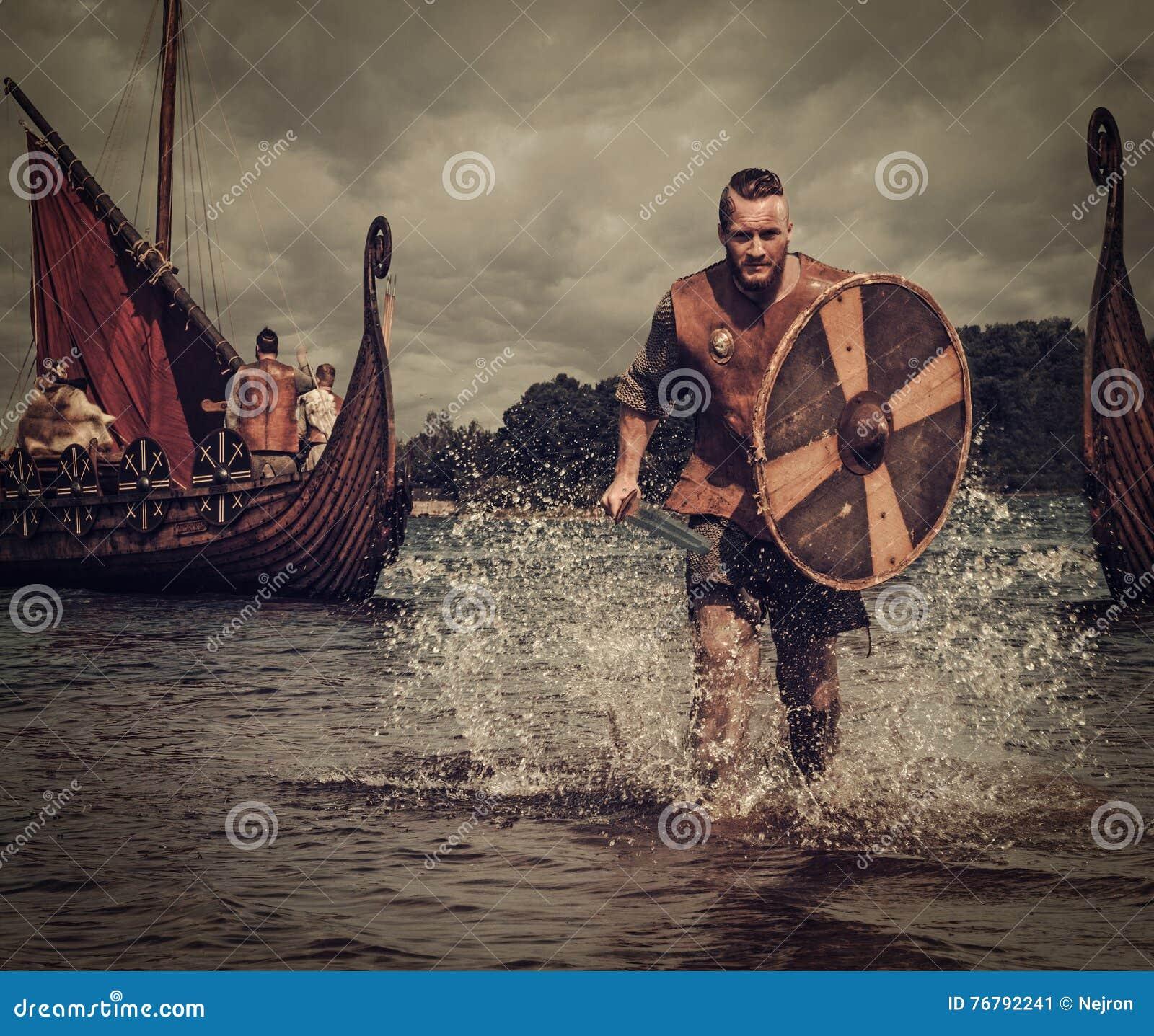 Guerriero di Viking nell attacco, corrente lungo la riva con Drakkar ai precedenti