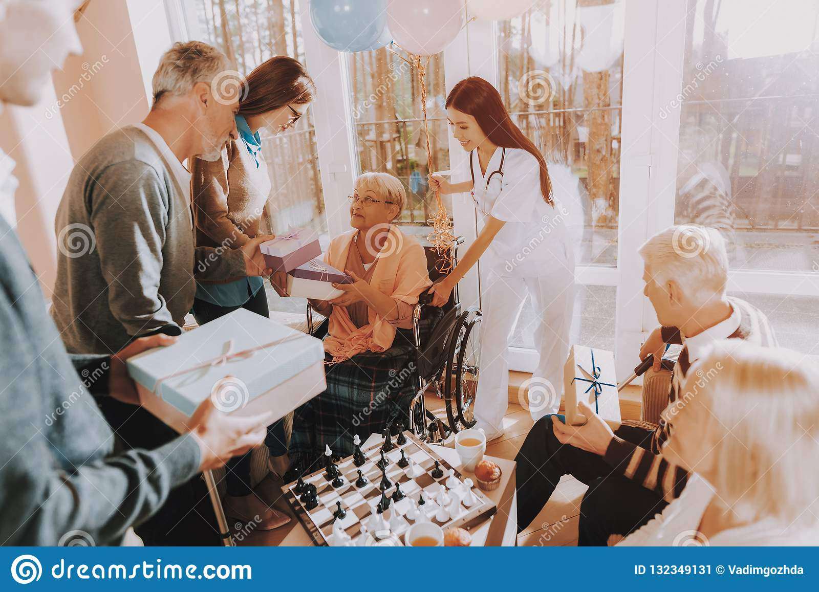 Guests Give Gifts To Elderly Woman Birthday Party Stock Image