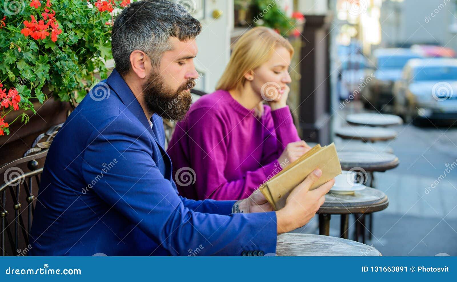Guia a datar Povos da reunião com interesses similares O homem e a mulher sentam o terraço do café A menina interessou que ele le