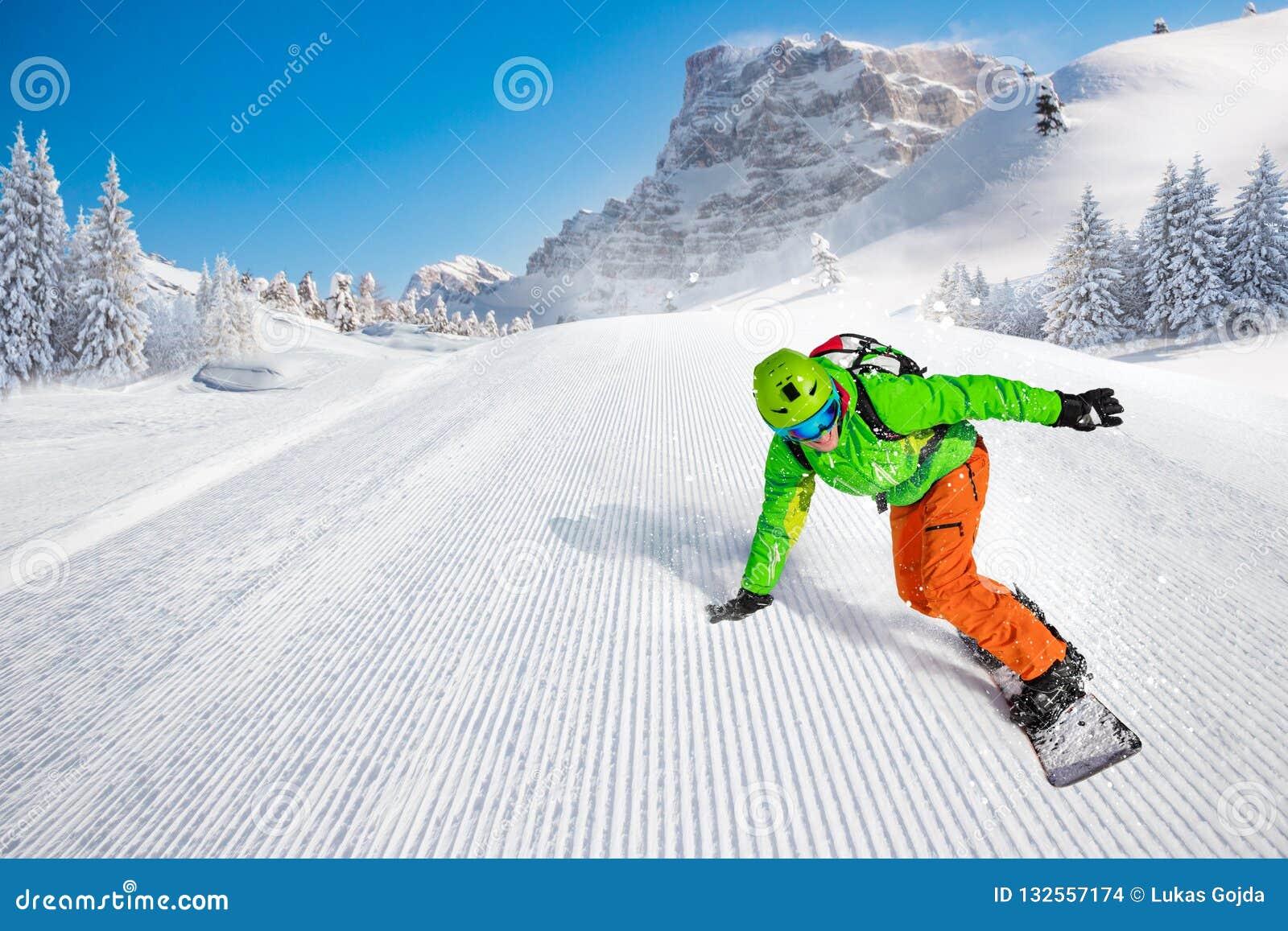 Guida dello snowboarder dell uomo sul pendio