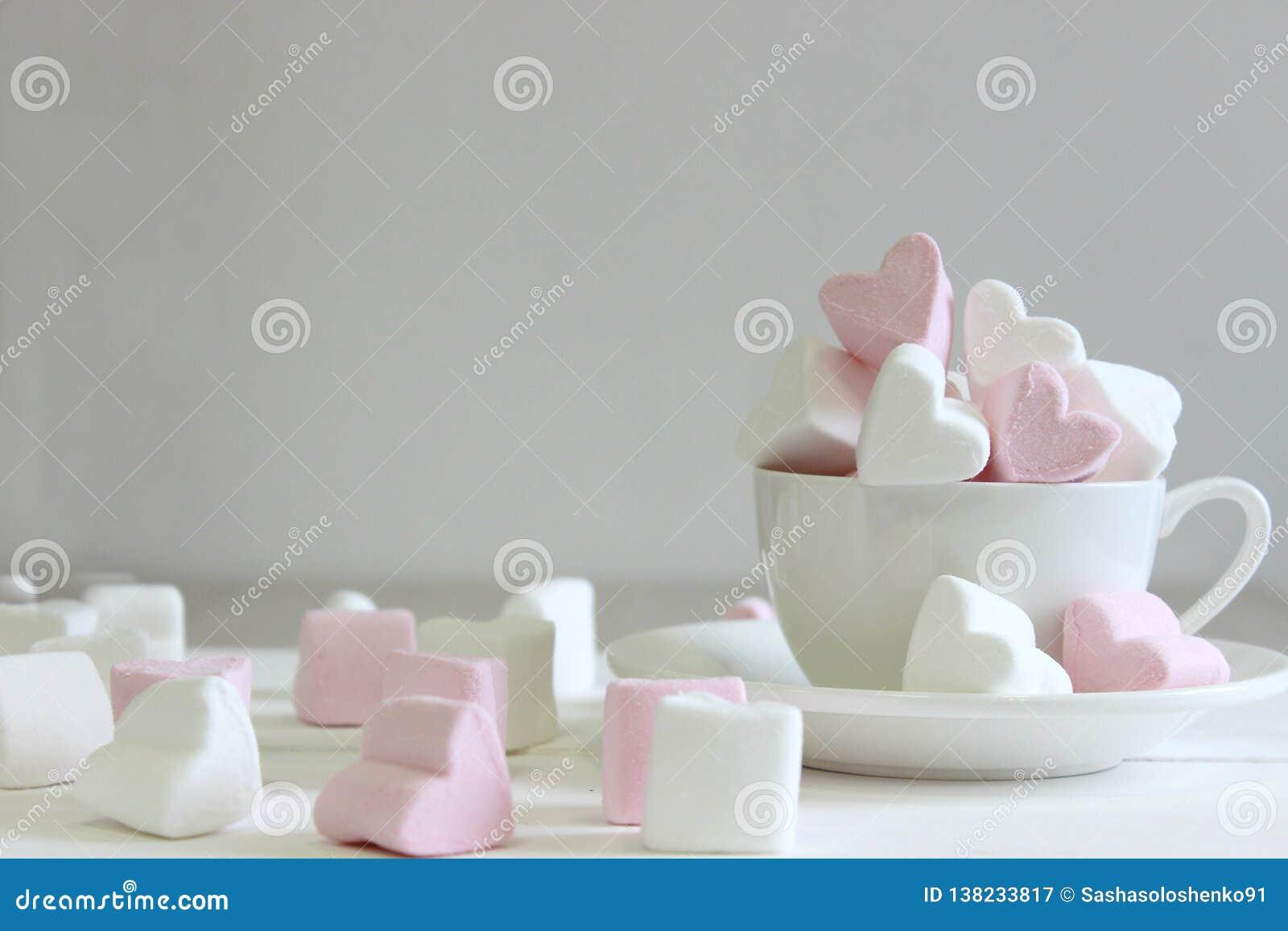 Guimauves douces sous forme de coeur dans la tasse en céramique avec le fond rose Concept au sujet de l amour et des relations St