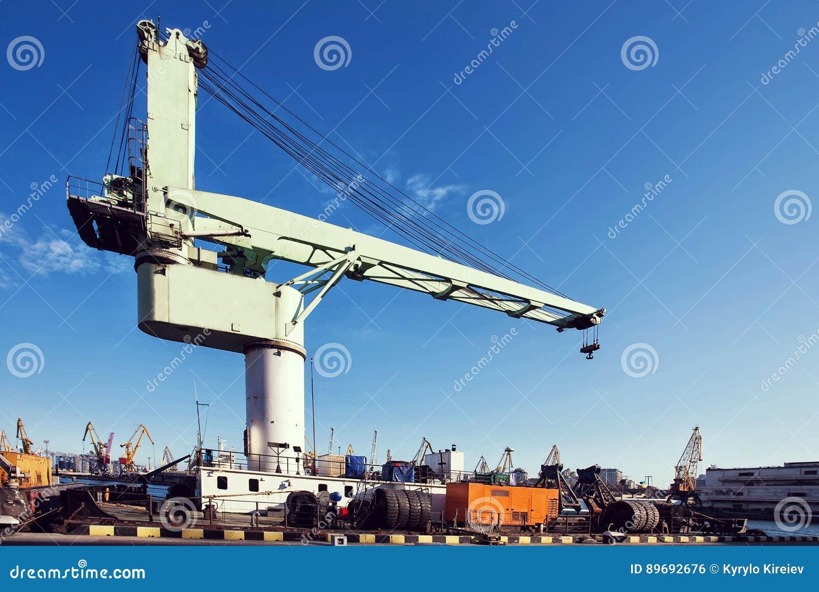 Guindaste da carga do porto sobre o fundo do céu azul Porto marítimo, guindaste para carregar no por do sol transporte