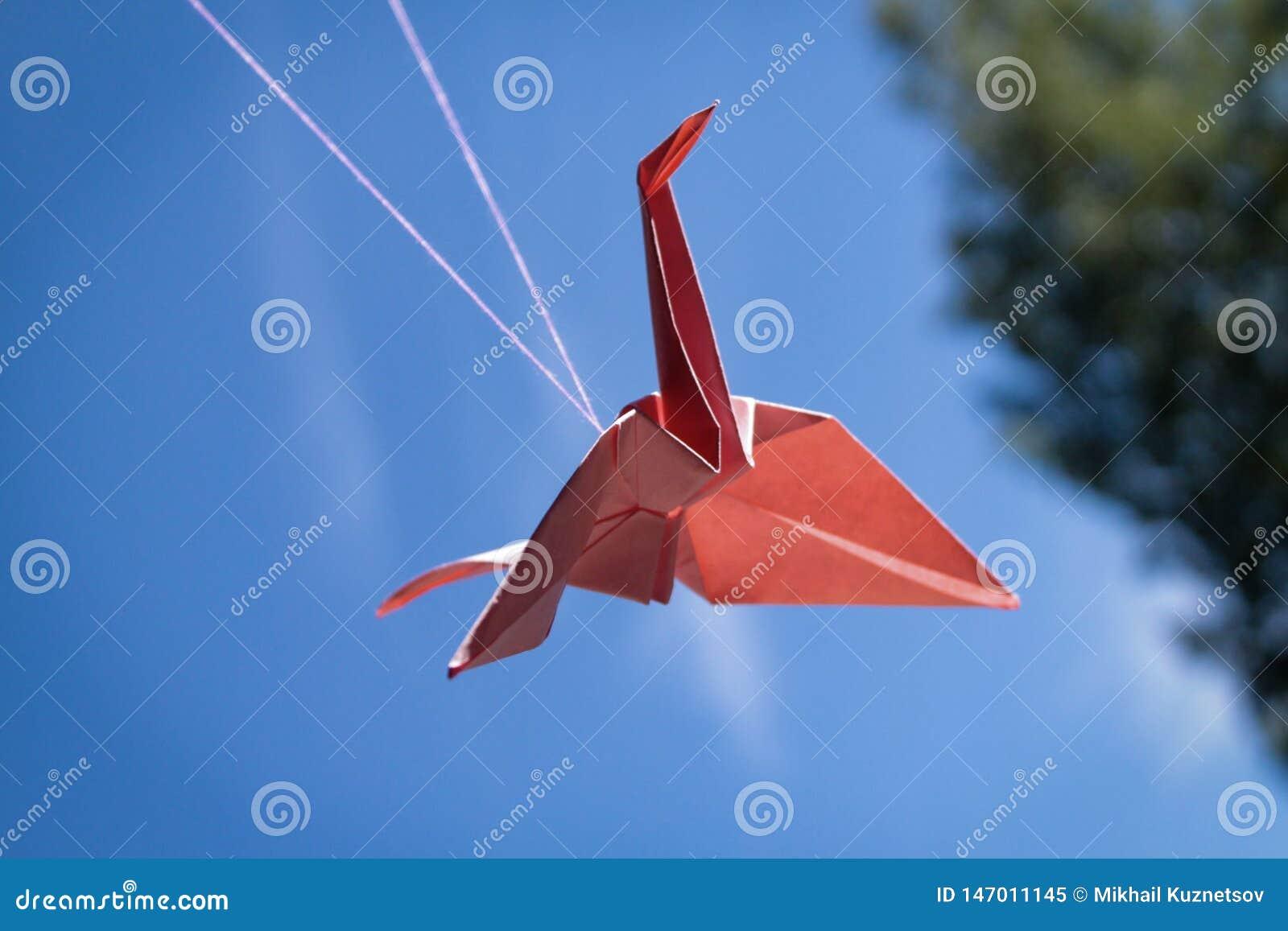 Guindaste de papel vermelho do origâmi do pássaro no céu