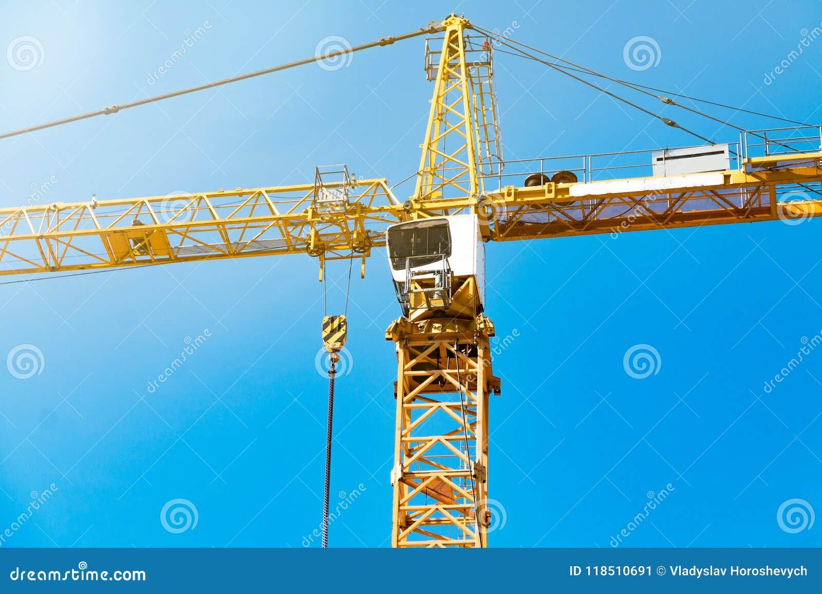 Guindaste de torre da cabina do piloto, guindaste de construção alto contra o céu azul, um guindaste com um contrapeso