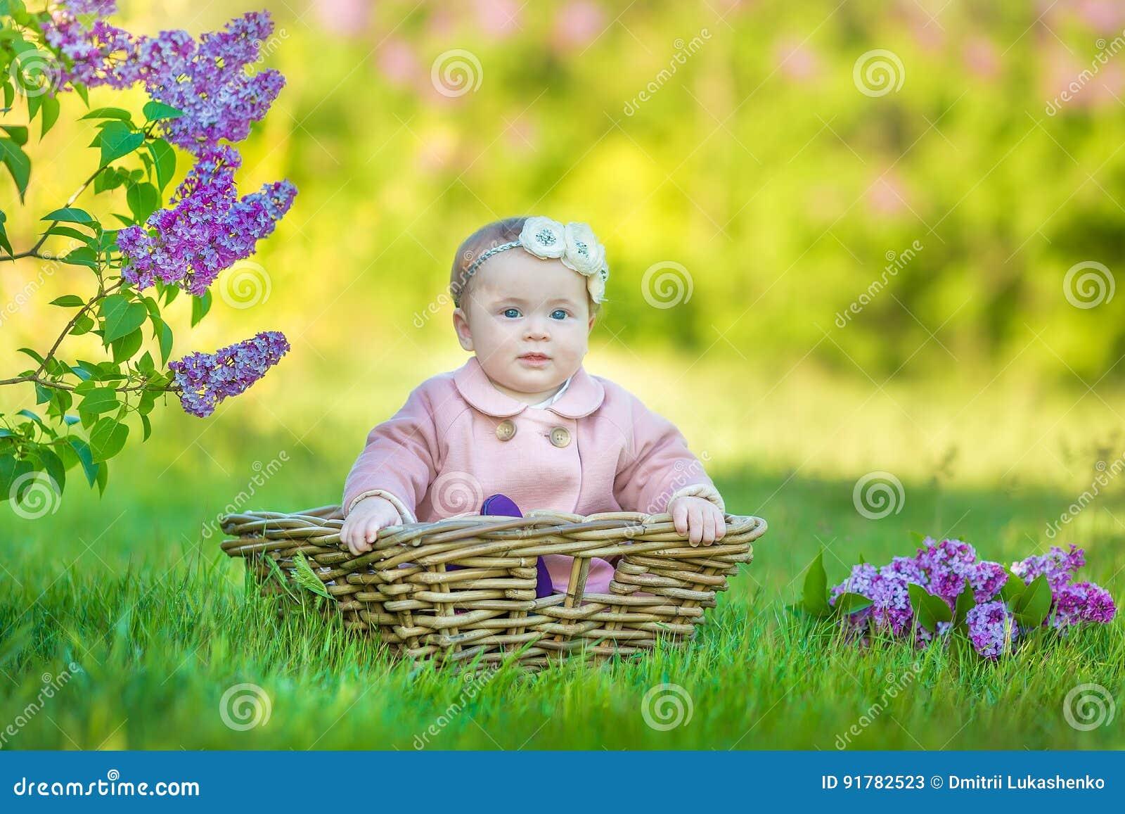 Guirlande de port an de sourire de fleur du bébé 1-2, tenant le bouquet du lilas dehors regarder l appareil-photo printemps d été