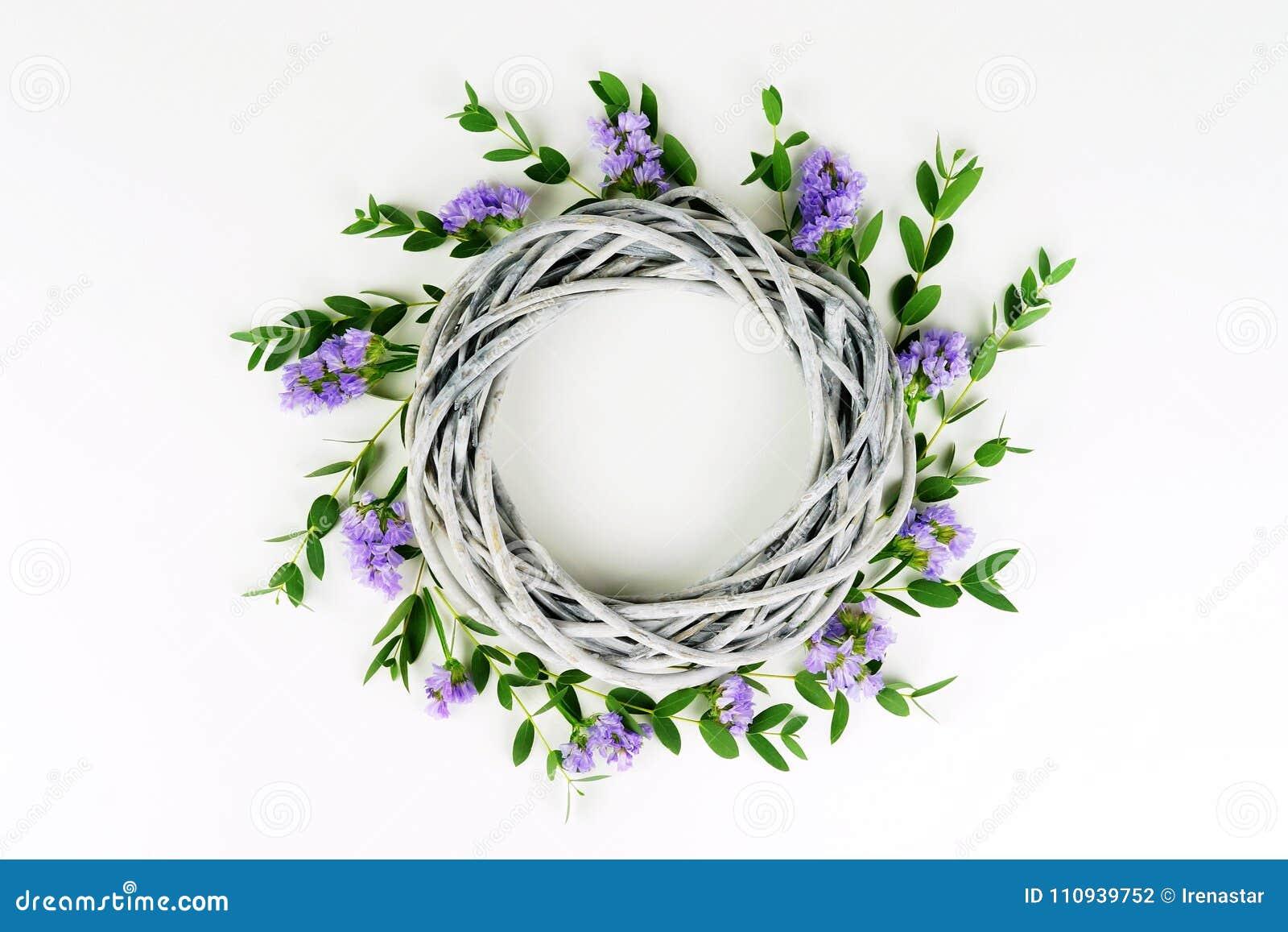Guirnalda hecha de círculo de mimbre, las ramas del eucalipto y flores púrpuras