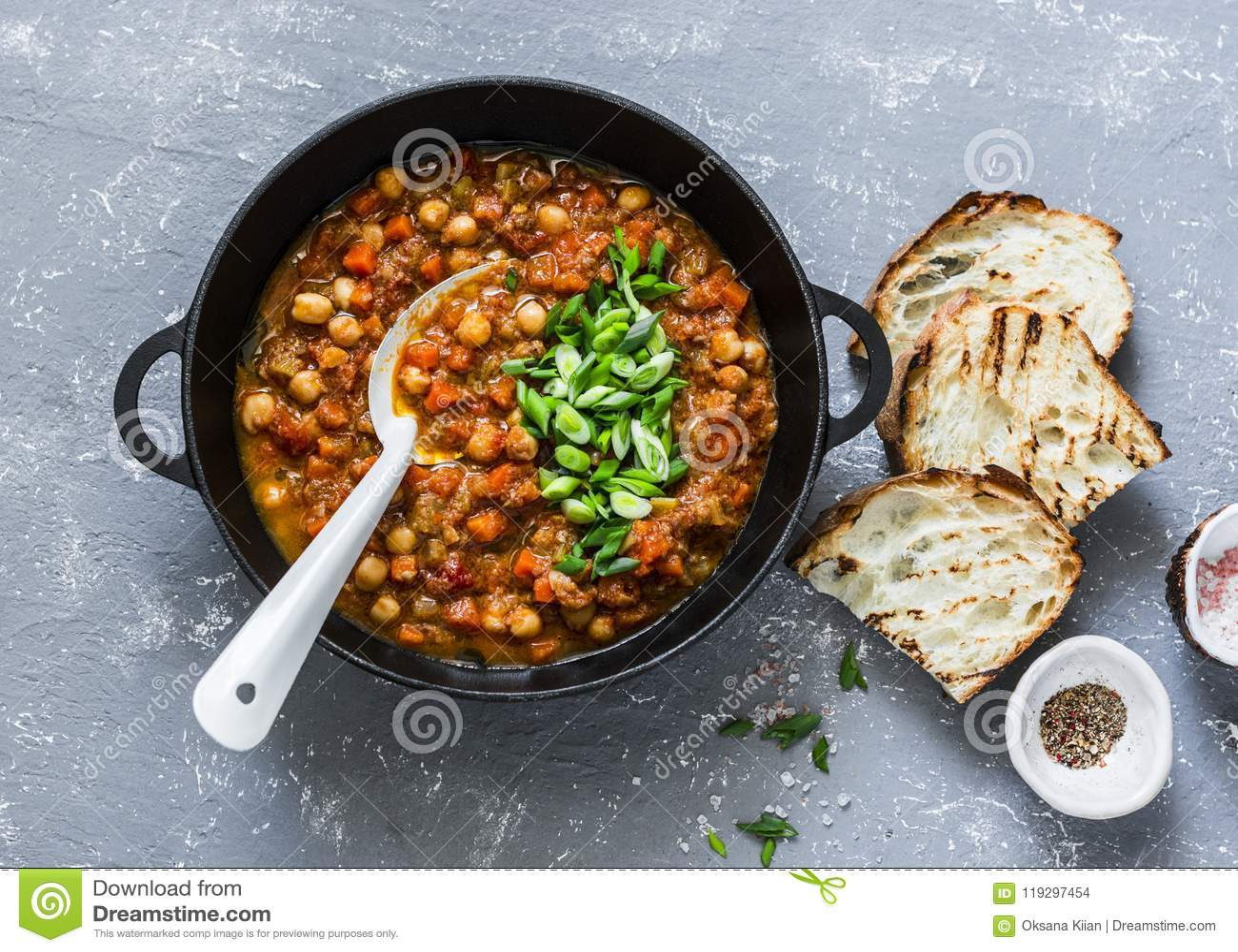 Guisado del garbanzo de las setas del vegetariano en una cacerola y un pan asado a la parrilla rústico en un fondo gris, visión s