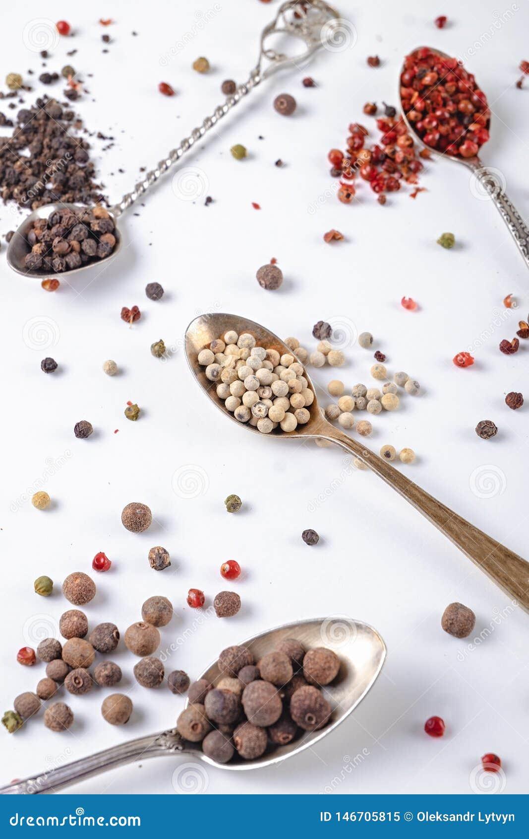 Guisantes de la pimienta negra, roja, blanca en cucharas del metal en un fondo blanco chile, paprika