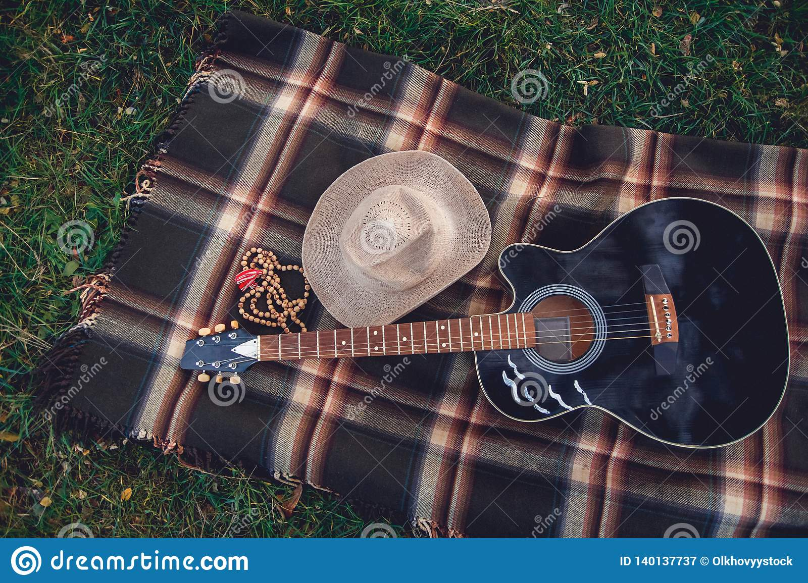 Guitar, basket, sandwiches, plaid and juice in a blossoming garden. Vintage tender background. Romance, love, date