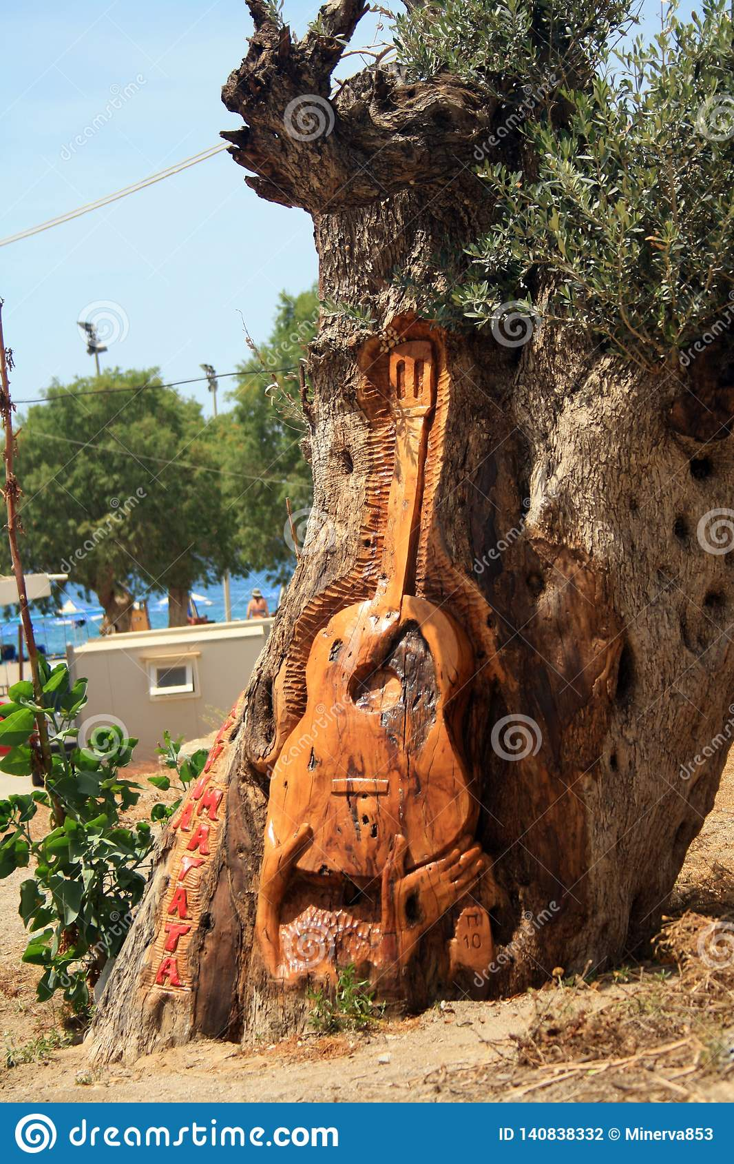 A guitar carved on the tree on the Matala beach on the Crete island