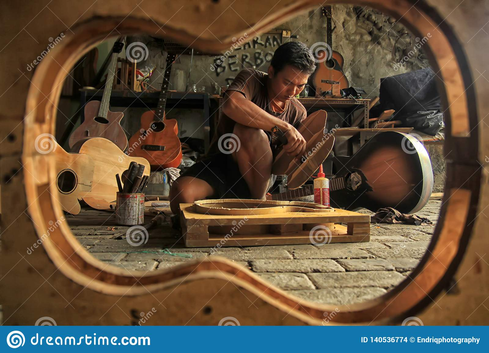 A guitar craftsman is busy making orders from his clients.