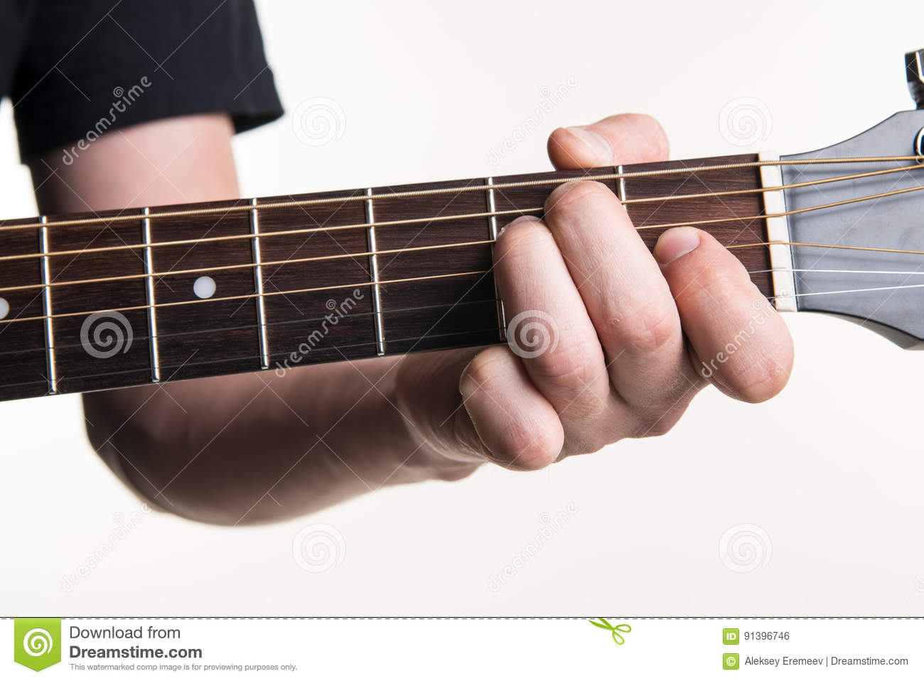 The Guitarists Hand Clamps The Chord E On The Guitar On A White