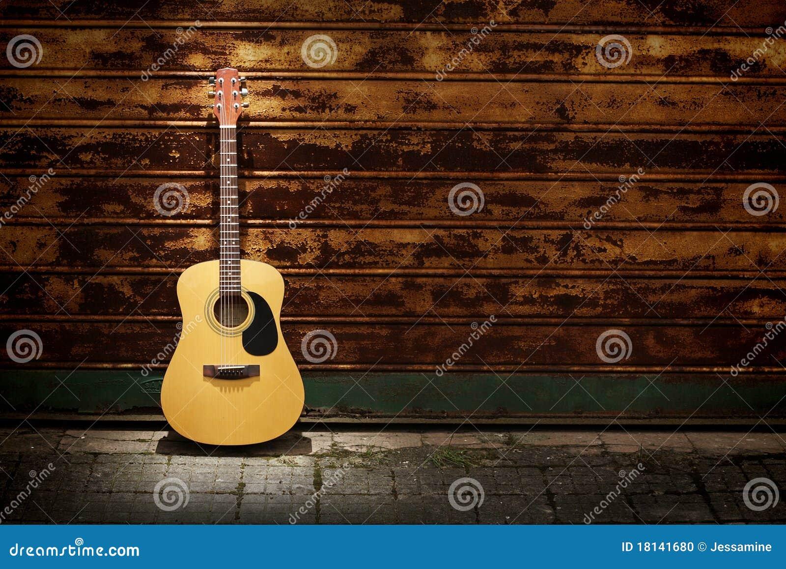 Guitarra acústica de encontro às portas oxidadas