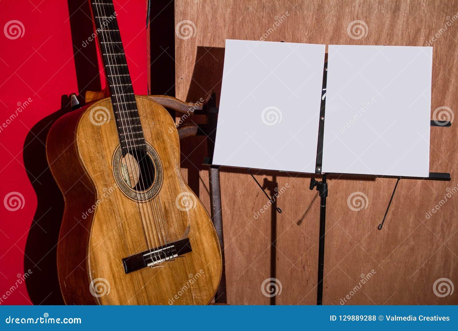 A guitarra, a cadeira e o atril indicaram com um fundo de madeira e vermelho