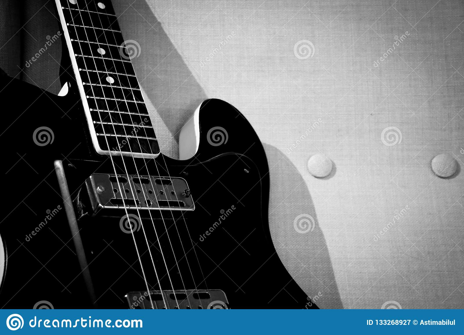 Guitarra do vintage em uma cadeira do braço do vintage