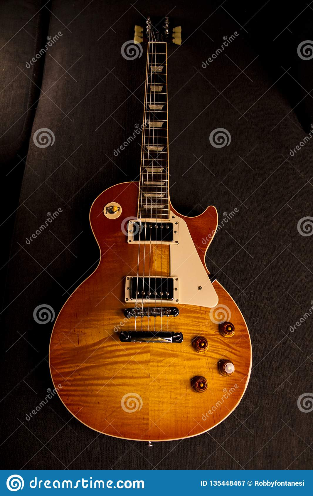 Guitarra eléctrica del vintage con la pintura perfecta de un color brillante de la cereza con reflexiones casi metálicas