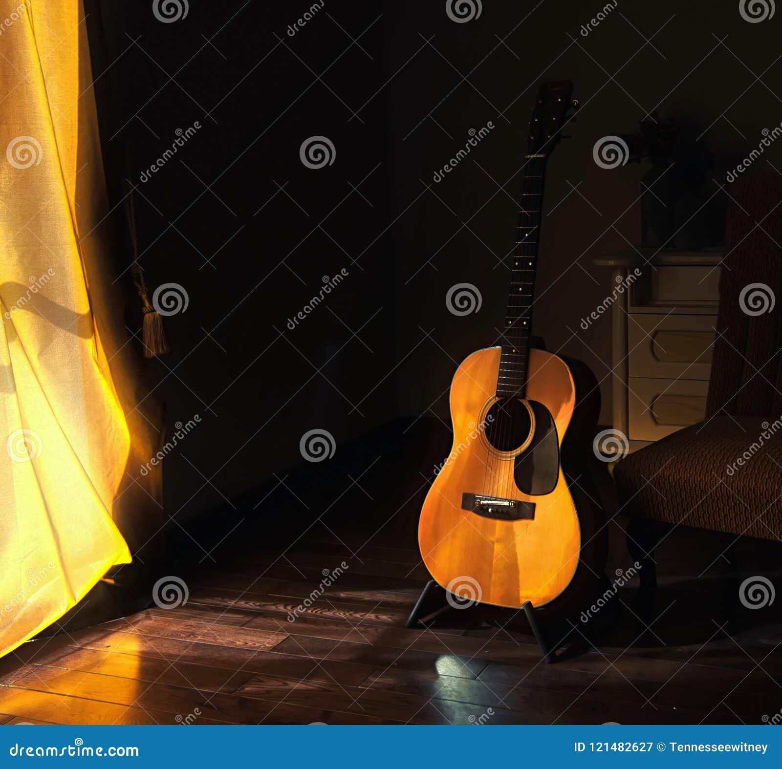 Guitarra espanhola acústica em um suporte nas sombras temperamentais de uma sala escura com a luz brilhante que vem dentro atrás