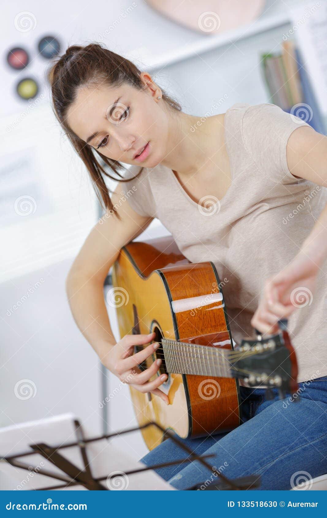 Guitarra que juega adolescente femenina en casa
