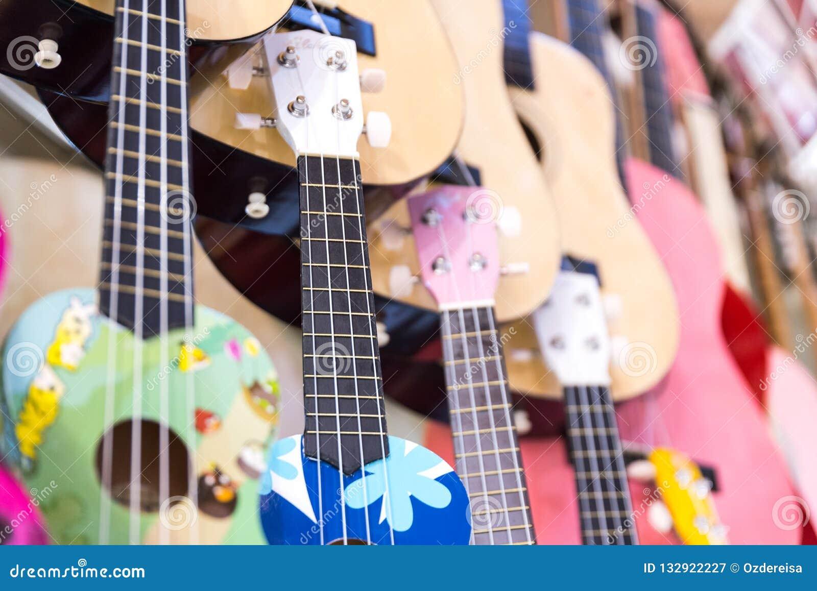 Guitarras de madera coloridas que cuelgan en la pared de la sala de exposición de la tienda