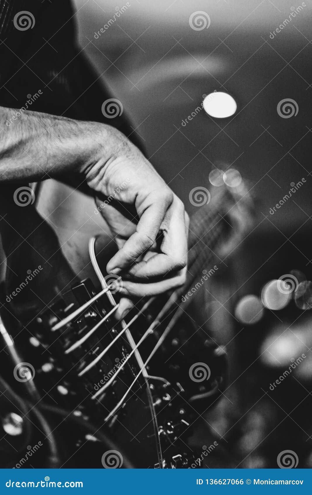 Guitarrista bajo que golpea ligeramente en un bajo de 5 secuencias durante un extracto de la demostración de la roca