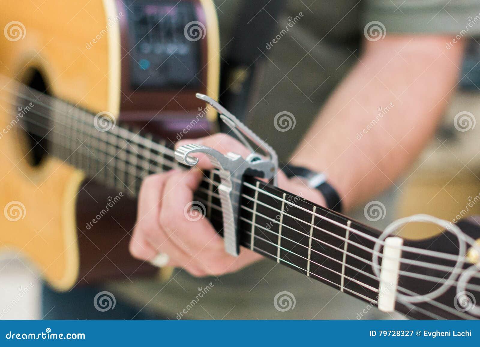 Guitarrista del hombre en la guitarra acústica