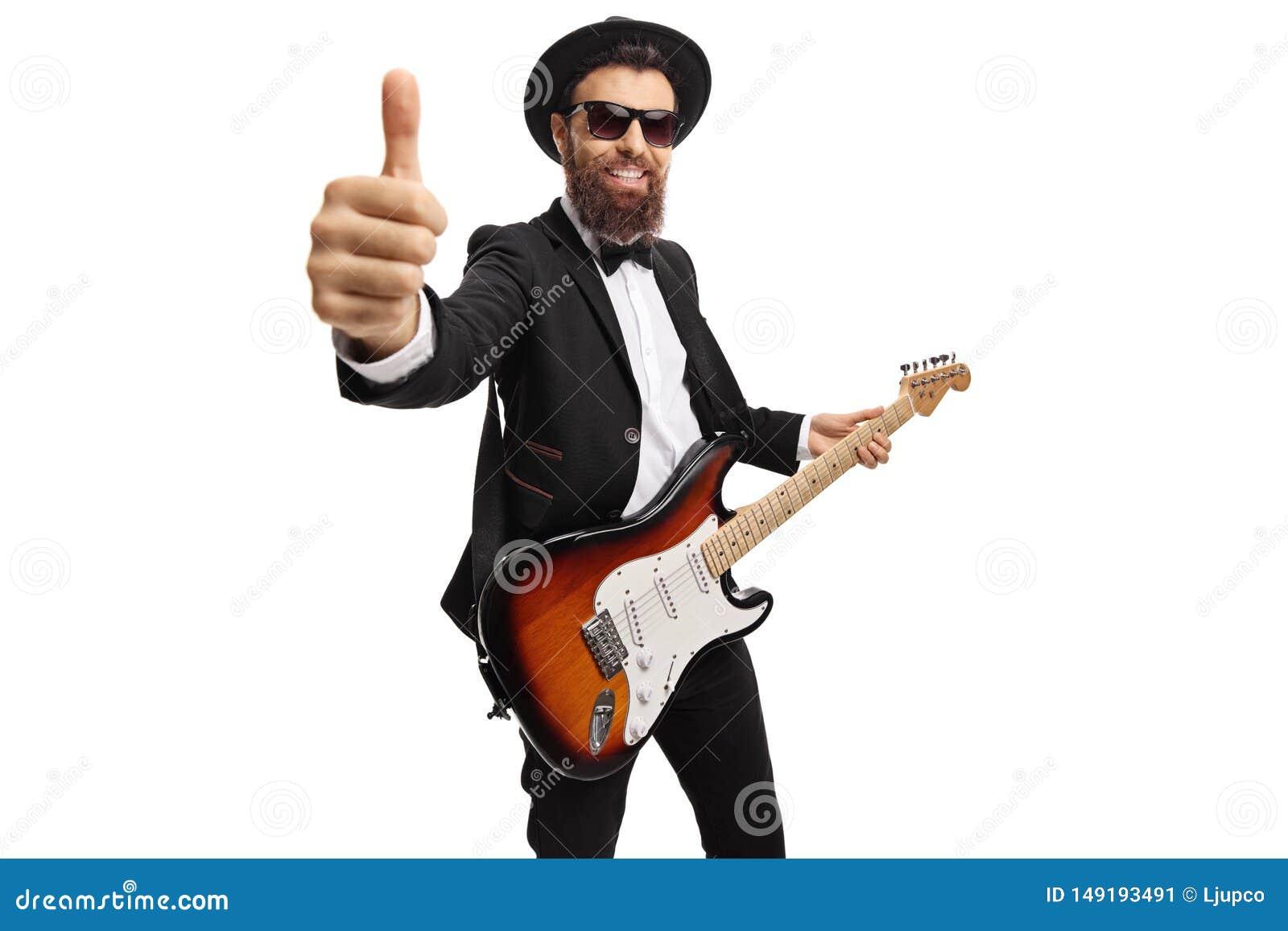 Guitarrista masculino alegre com uma guitarra el?trica que mostra os polegares acima