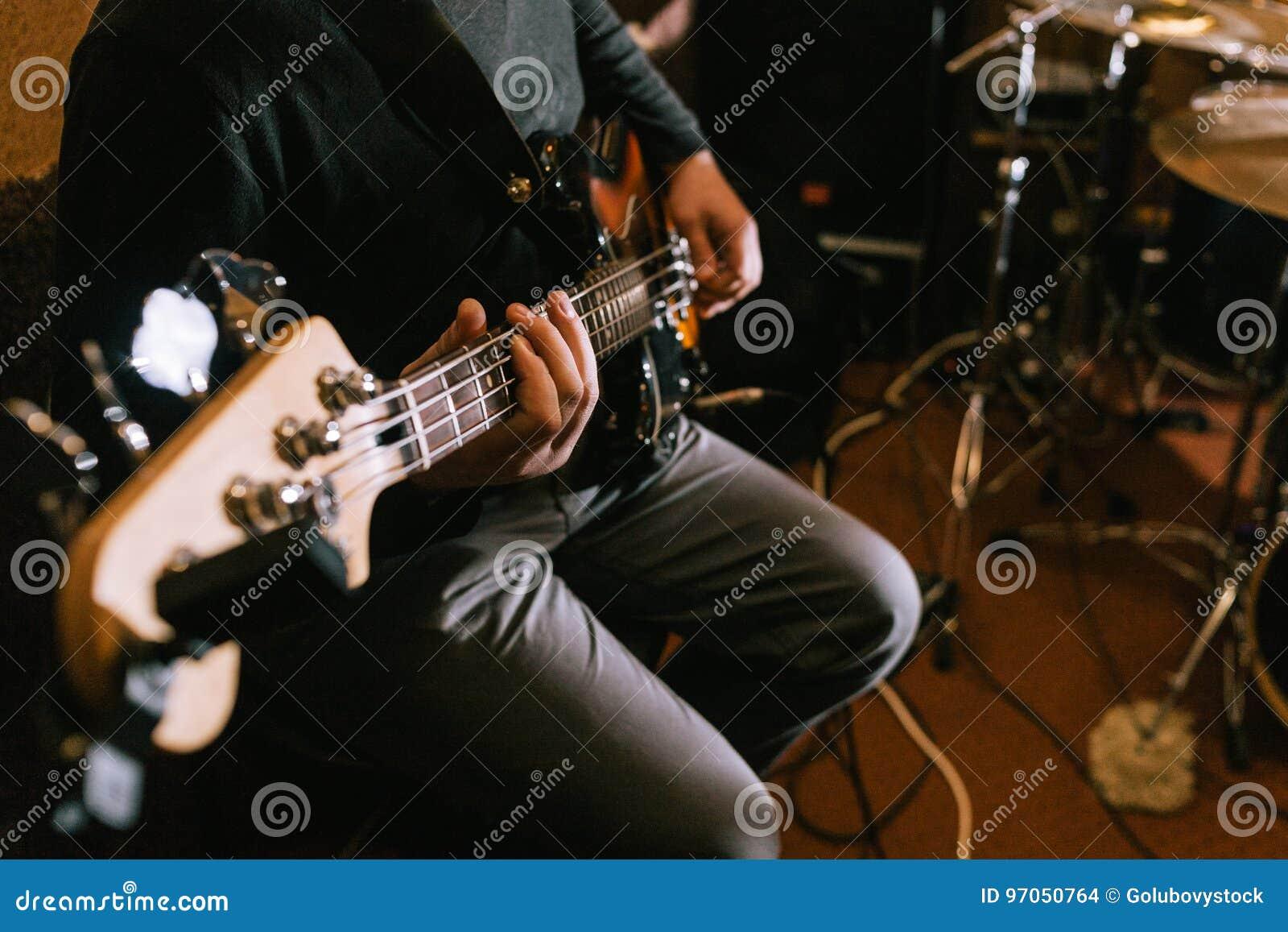 Guitarrista que toca la guitarra baja en primer del estudio
