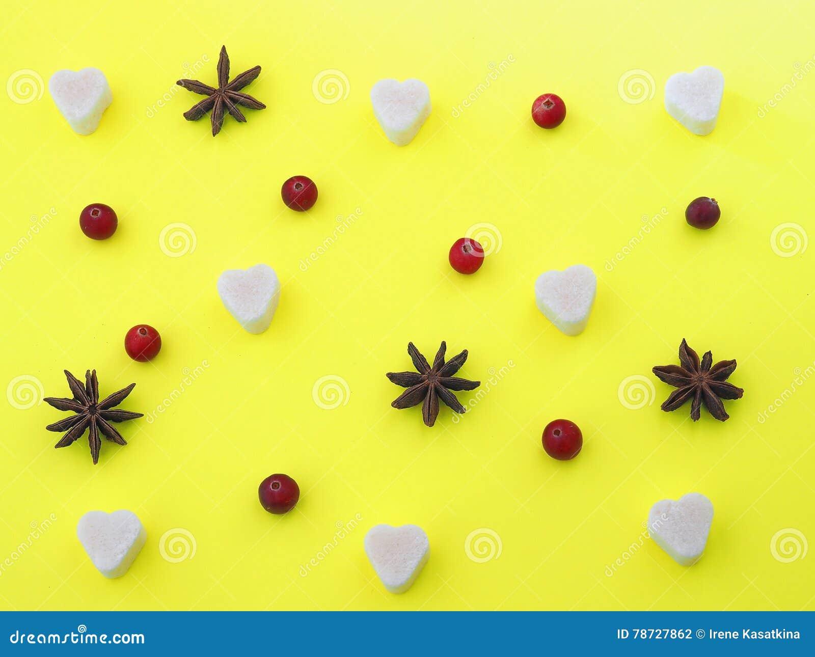 Gul bakgrund med sockerhjärta, anisstjärnor och tranbär