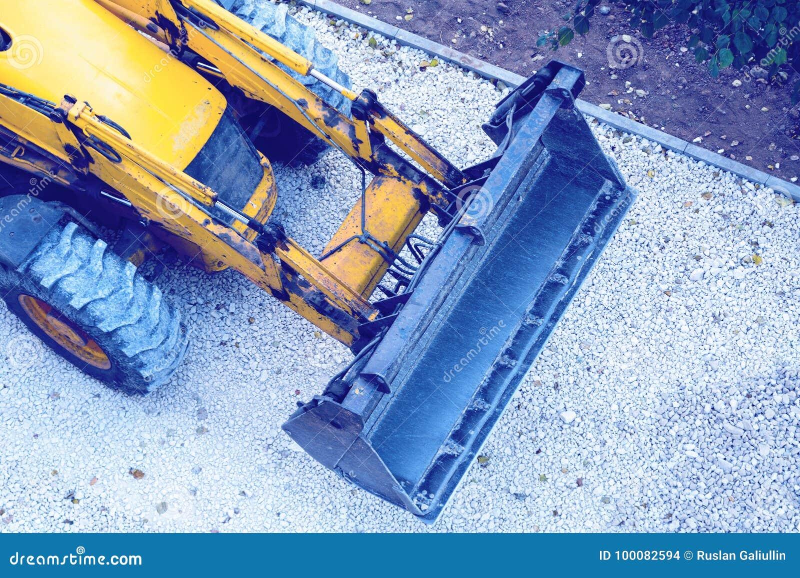 Gul bulldozer som laddar grus för vägkonstruktion