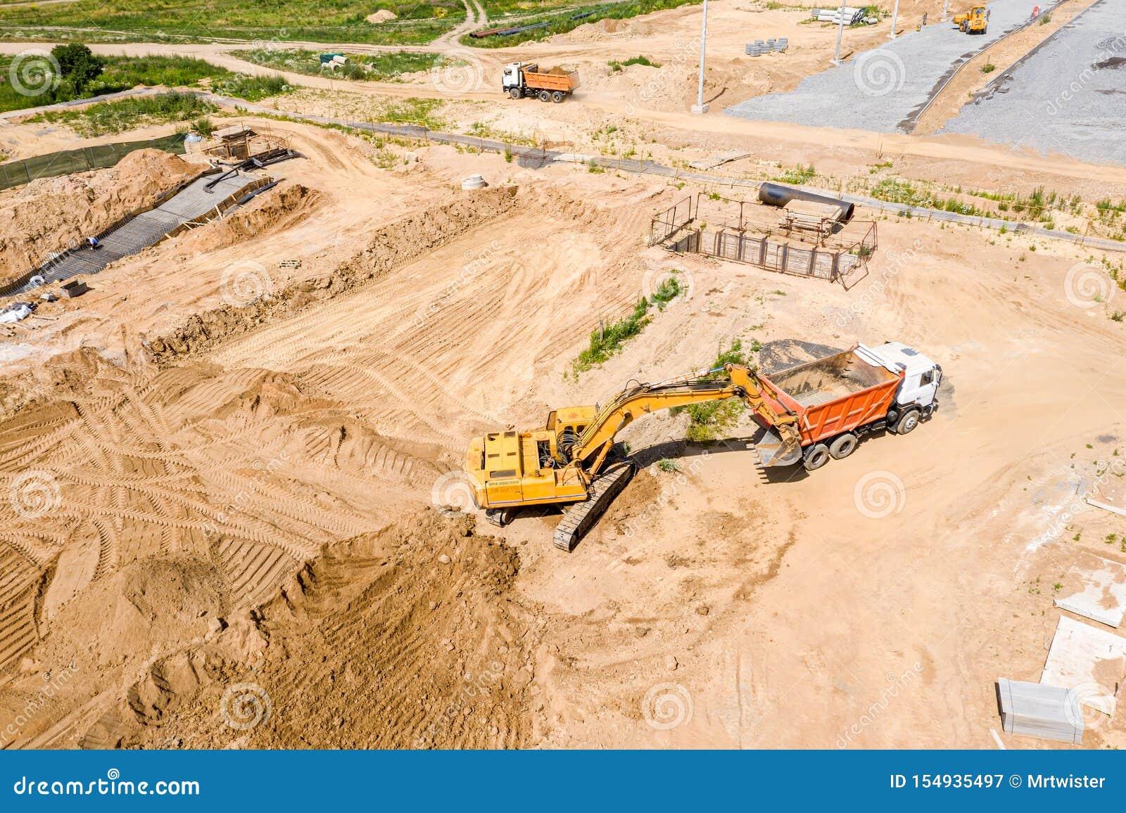 Gul grävskopa som laddar jordning i dumper på konstruktionsplatsen