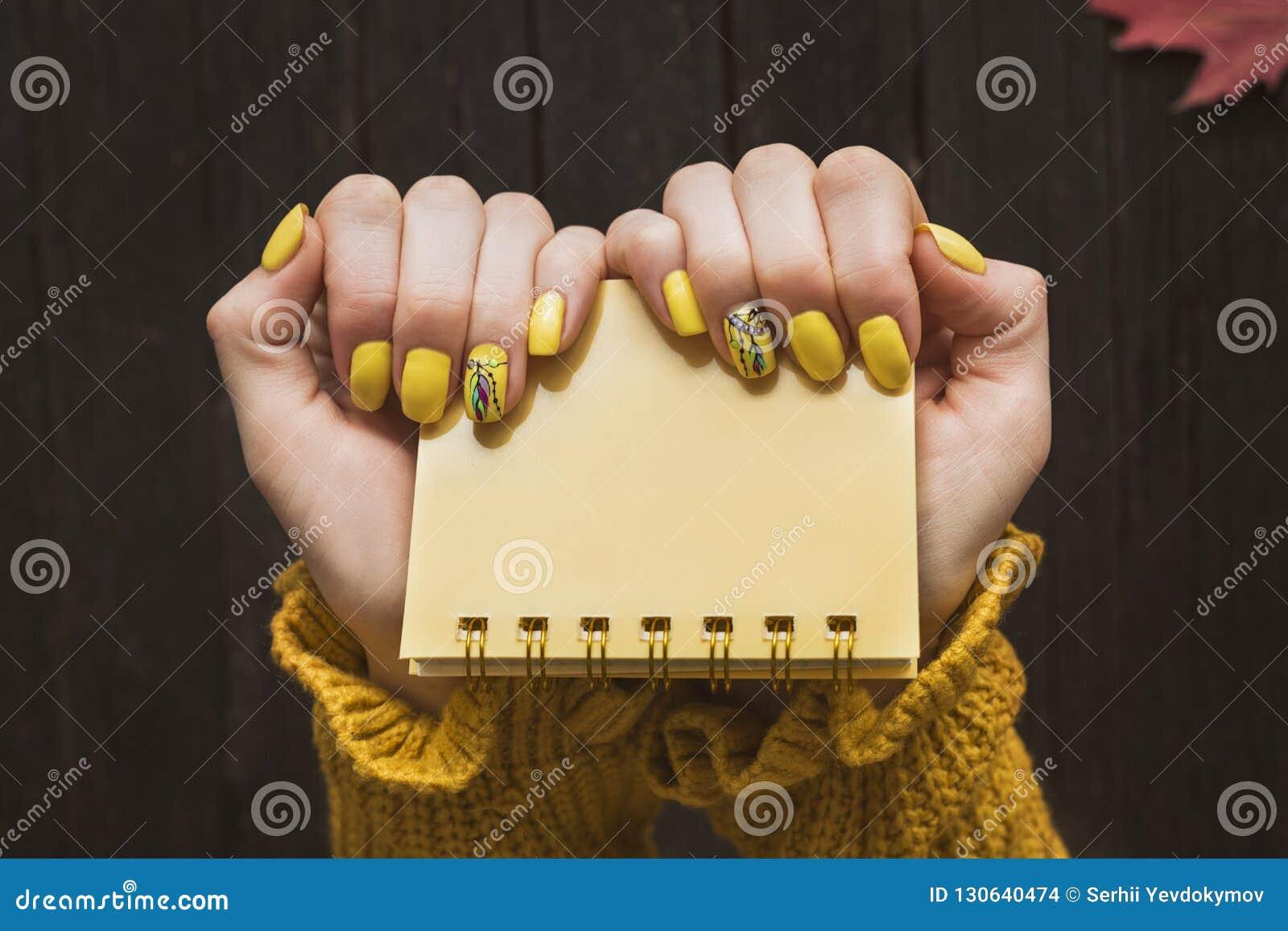 Gul notepad i kvinnliga händer Manikyr med en modell Slut-u