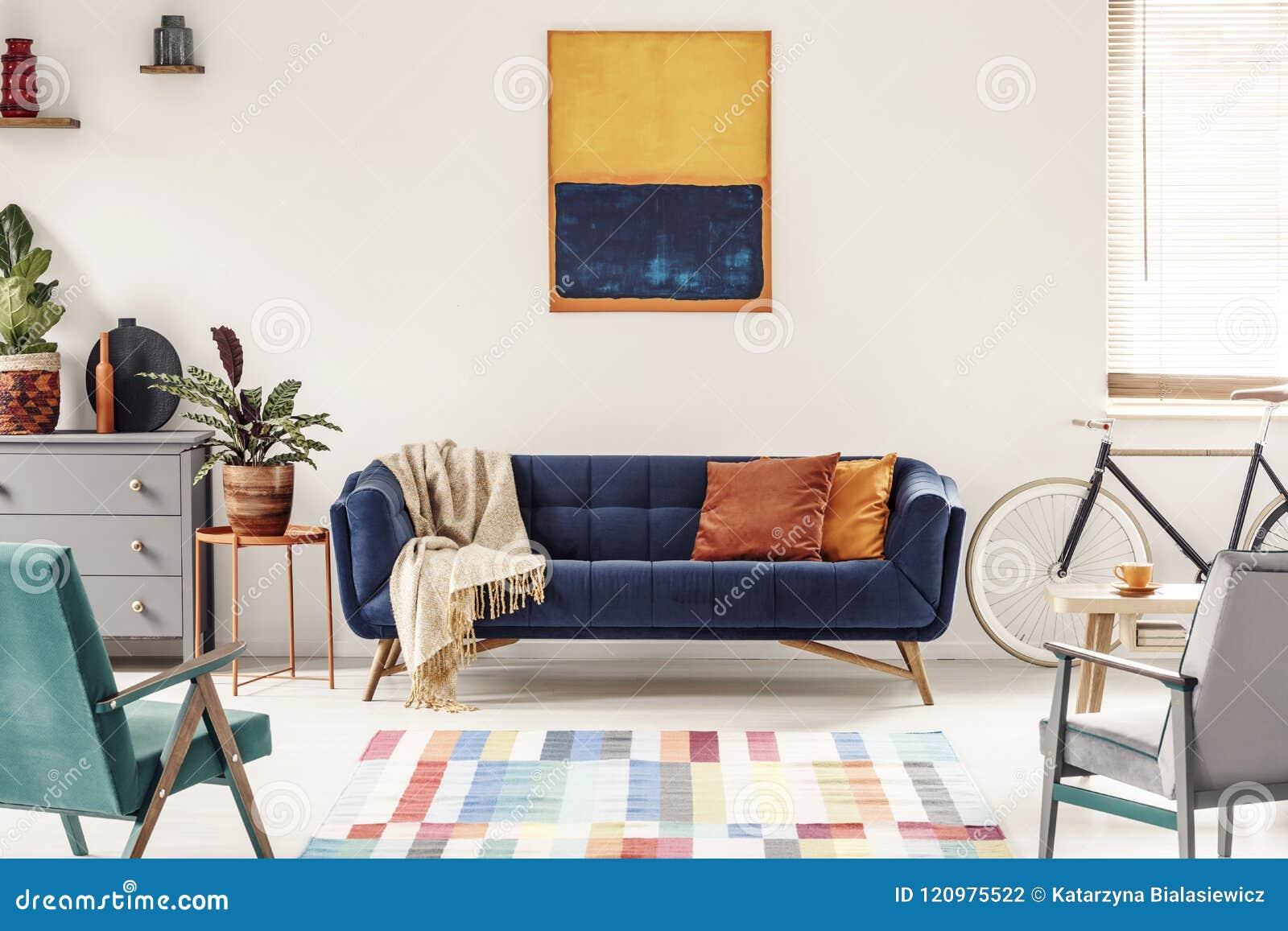 Gul och marinblå målning ovanför soffan i modern vardagsrum I