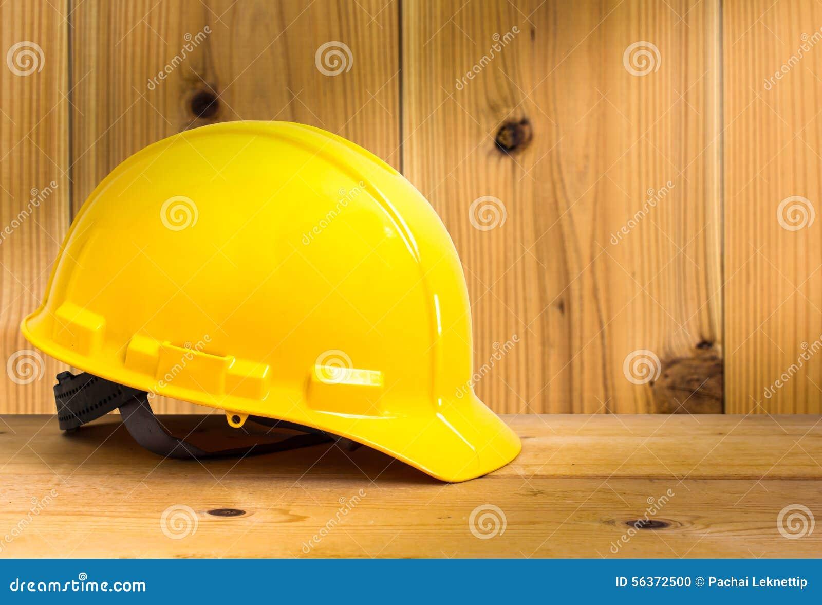 Gul säkerhetshjälm på trägolv med Wood väggbakgrund,