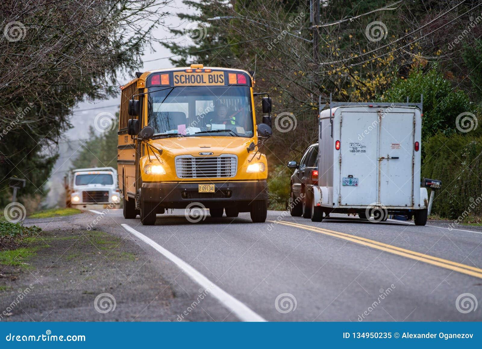 Gul skolbuss som kör på en gata