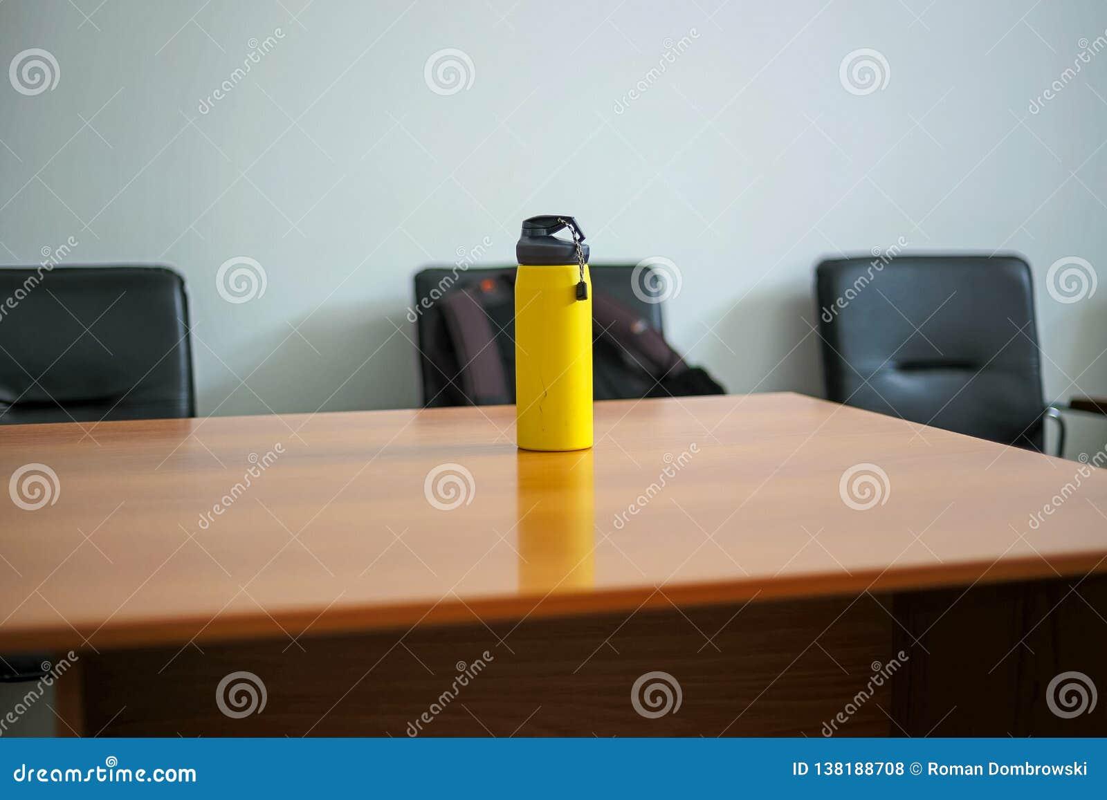 Gul sportflaska med vatten på en trätabell Selektivt fokusera