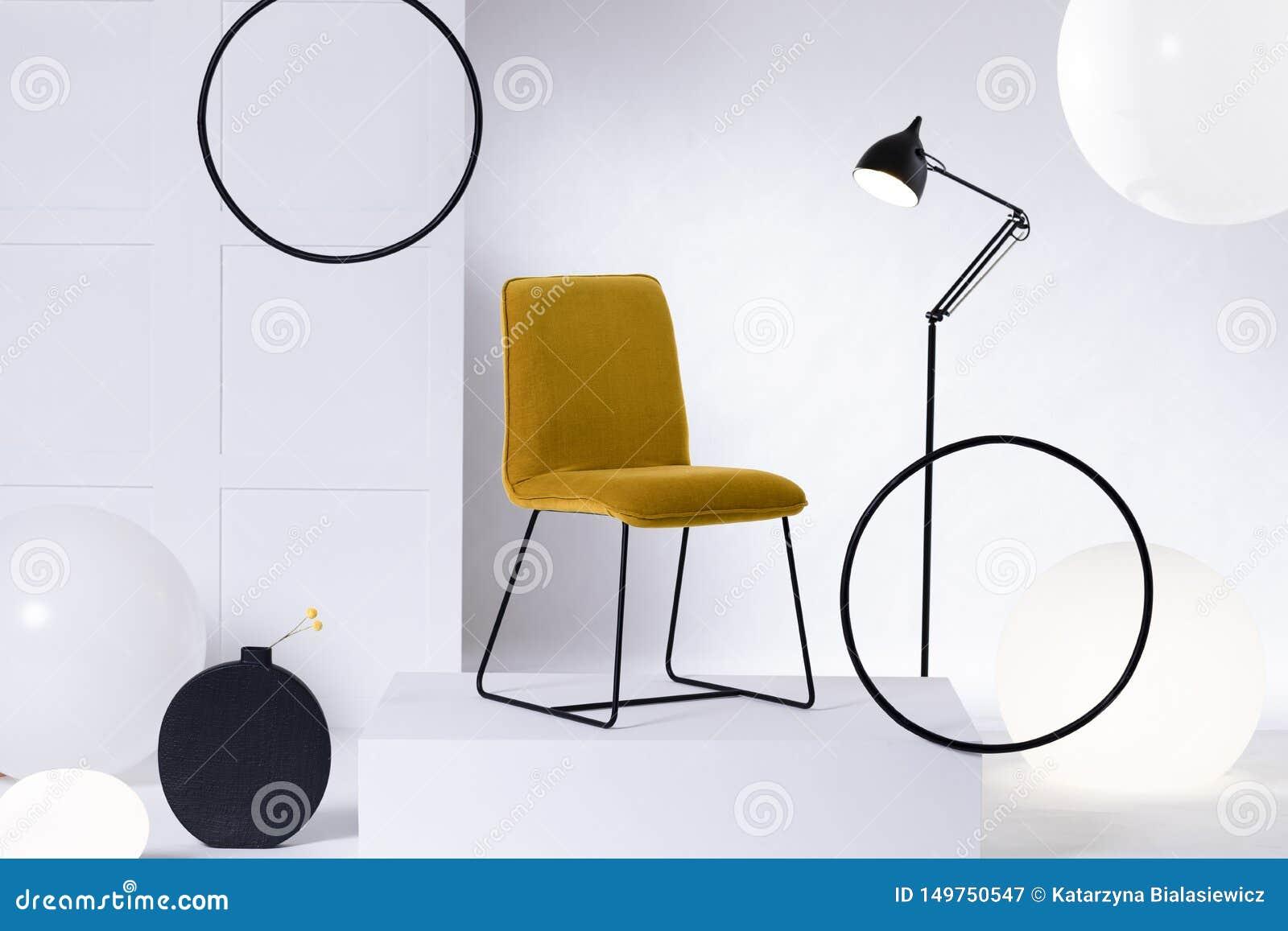Gul stol f?r stilfull sammet bredvid den h?gv?xta industriella svarta lampan i den vita inre