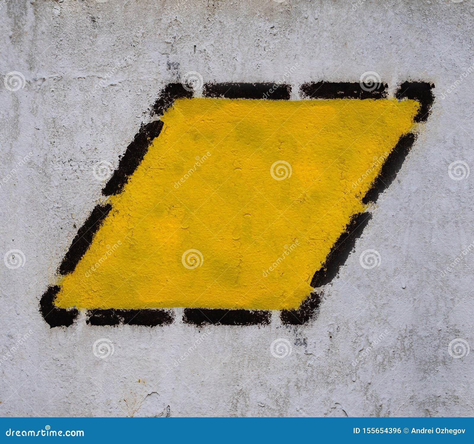 Gul triangel, fyrkant, romb i svart prickig ram på den gamla gemensamma väggen