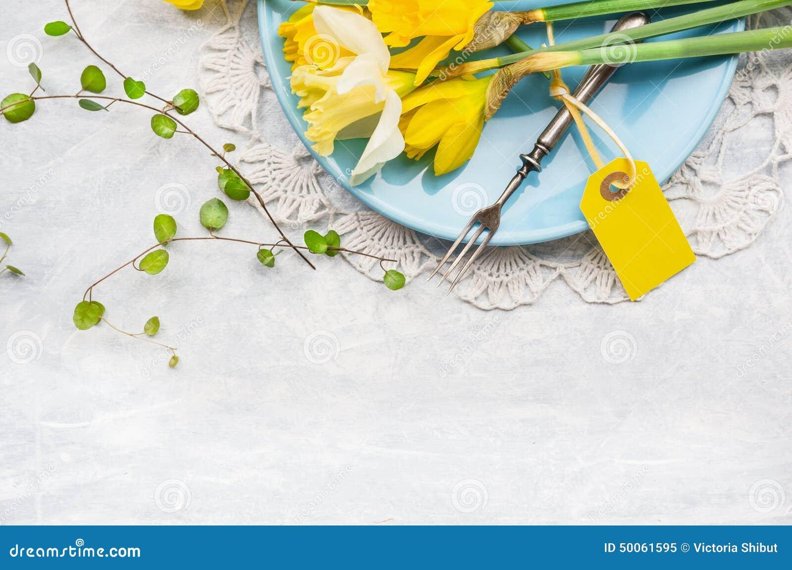 Gula påskliljor på blåttplattan med gaffeln och tabellen undertecknar, fjädrar garnering