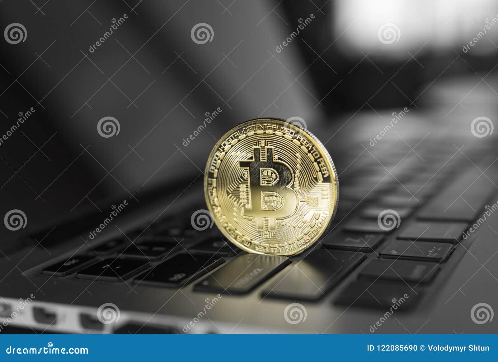 Guld- Bitcoin crypto mynt på ett bärbar datortangentbord Utbyte affär, reklamfilm Vinst från att bryta kryptavalutor
